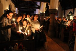 A photo of a candlelit carol service at All Saints Cheadle Hulme