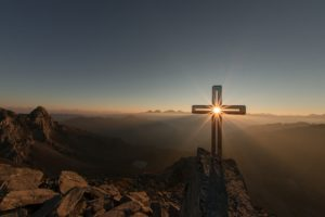 Photo of a cross on top of a mountain highlighted by the rising sun